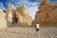 kvinde gaar paa sandstrand med flotte klipper i Oman