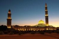 oplyst palads og solnedgang i Oman