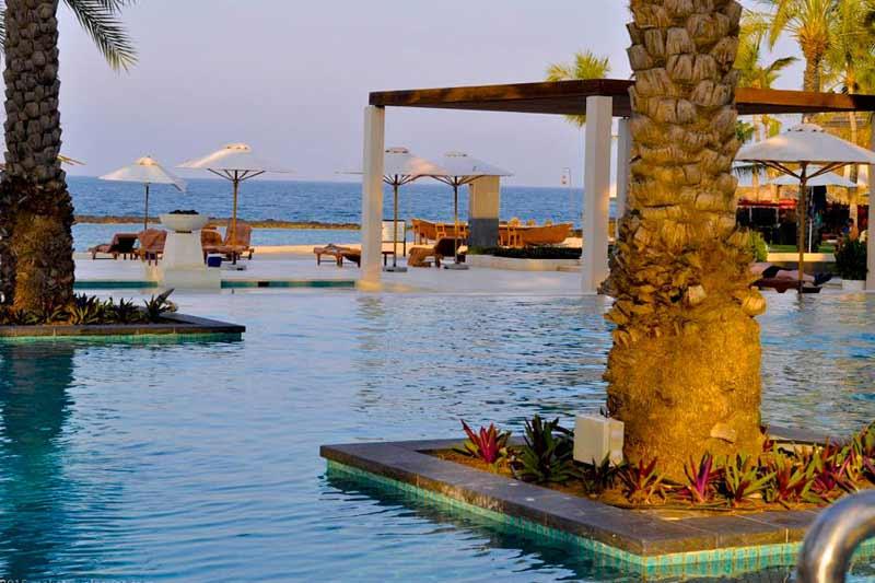 pool, parasoler og palmer i Oman