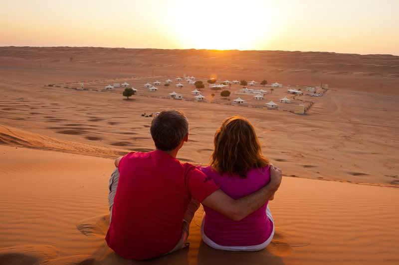 kærestepar nyder solnedgangen over ørkenen i Oman
