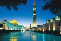 Flot oplyst palads og moske i en solnedgang i Oman